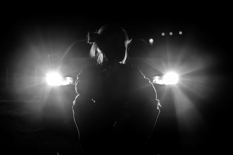 Rear view of silhouette woman standing against illuminated lights at night