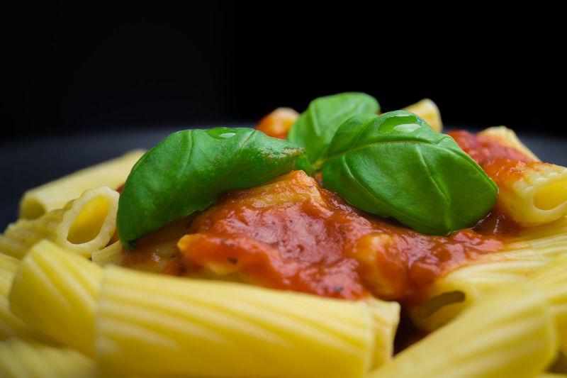 Close-Up Of Basil On Fresh Penne Pasta Served Against Black Background