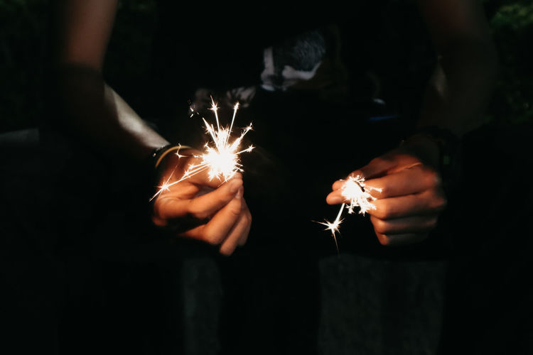 Midsection of person holding illuminated sparklers at night