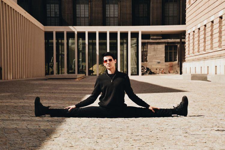 Portrait of young man sitting on sidewalk in city