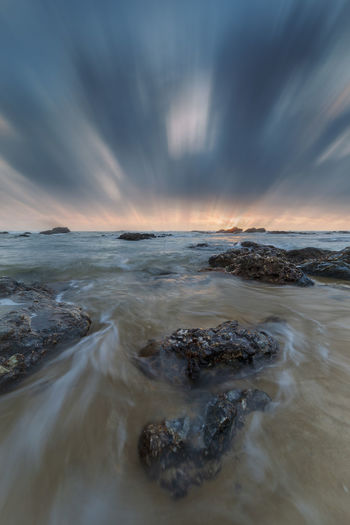 Beach side, waves and rocks with dramatic motion blur effect of clouds. Water Sky Sea Cloud - Sky Motion Scenics - Nature Beauty In Nature Land Beach Rock No People Sunset Long Exposure Nature Horizon Over Water Solid Wave Rock - Object Horizon Outdoors Power In Nature