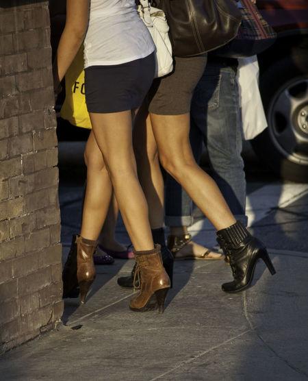 Low section of women walking on sidewalk