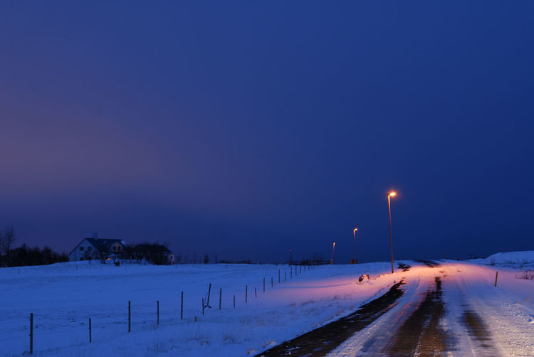 Road on snow covered field against clear blue sky at night