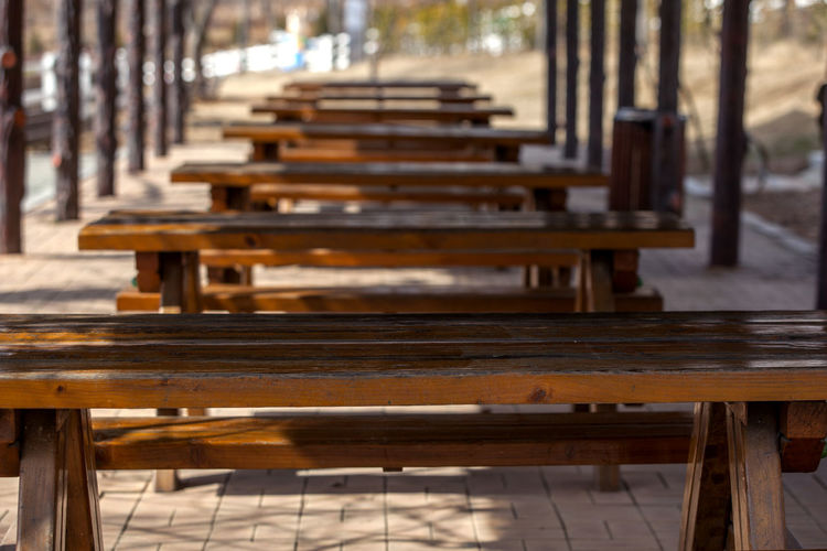Empty Wooden Picnic Tables In Park