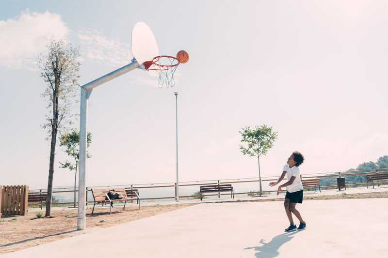 Full length of basketball hoop on street against sky