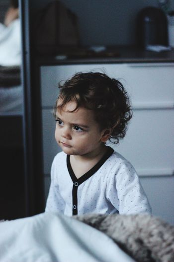 Baby frowning curiously in bedroom, looking away from camera
