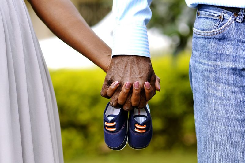 Midsection of couple holding hands with baby booties at park