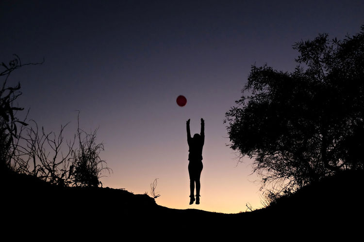 Low angle view of silhouette woman with arms raised jumping on hill against clear sky during sunset