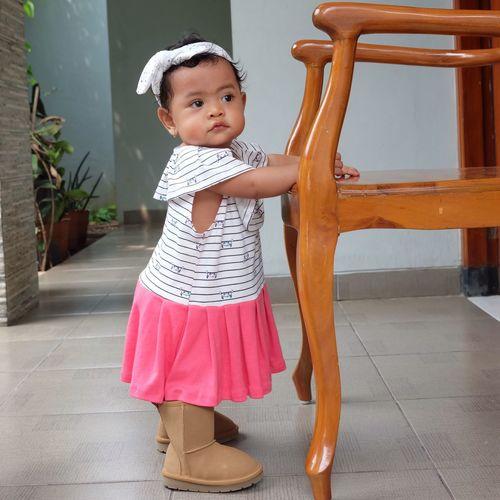 Full length of girl sitting on chair