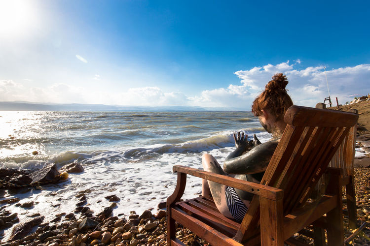 Side view of woman applying mud while sitting on chair at beach against sky