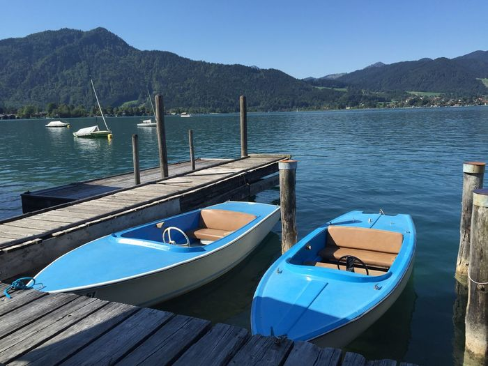 Boats Moored By Jetty In Tegernsee Lake Against Mountains