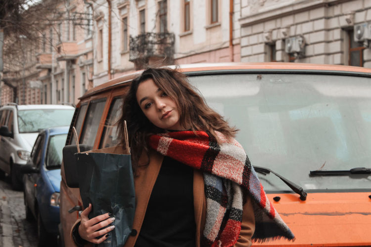 Woman in traditional clothing in city cars