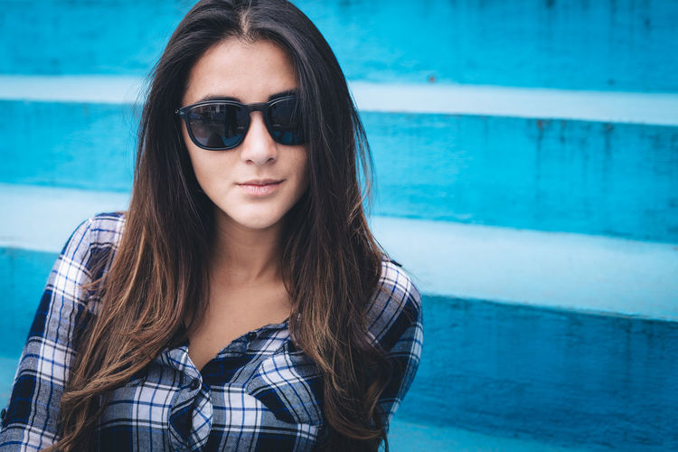 Portrait of beautiful young woman wearing sunglasses against wall