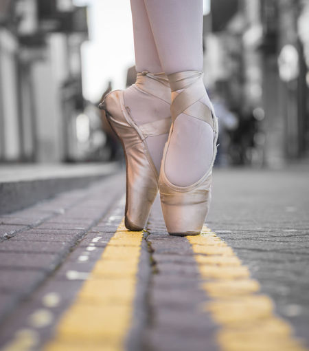 Low section of female ballet dancer dancing on road