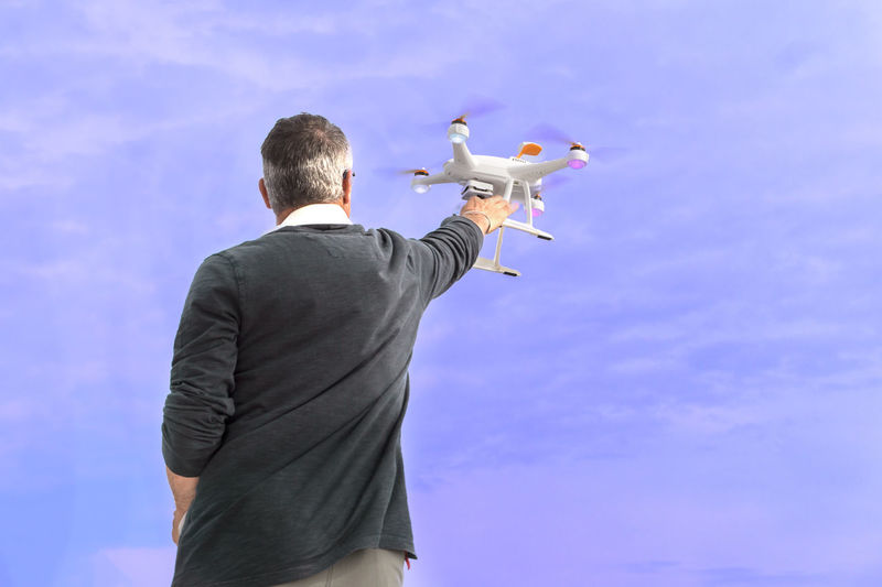 Rear view of man holding seagull
