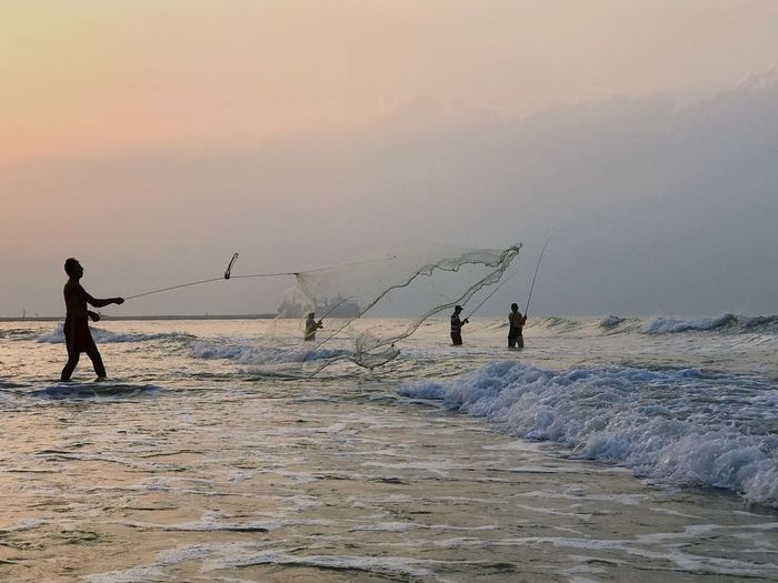 People fishing in sea against sky during sunset