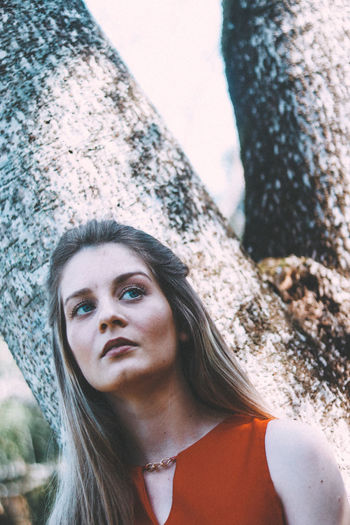 Close-up portrait of young woman against tree trunk