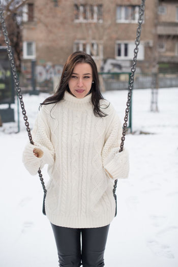 Young woman swinging in snow covered playground