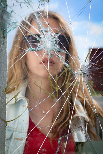 Reflection of young woman on broken mirror