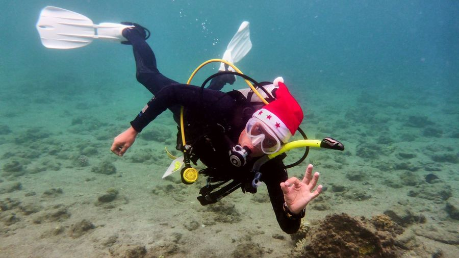Portrait of mid adult scuba diver showing ok sign while swimming in sea