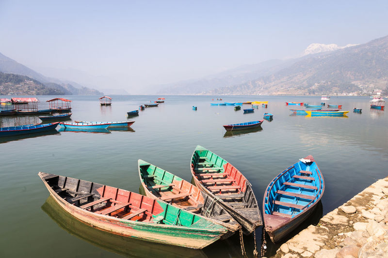 Boats moored on sea against mountains
