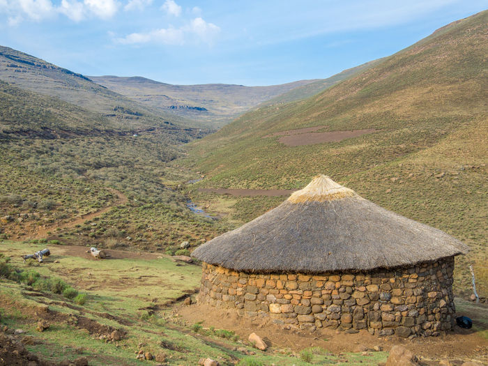 Scenic view of traditional basotho stone round hut in mountains against sky, lesotho, africa