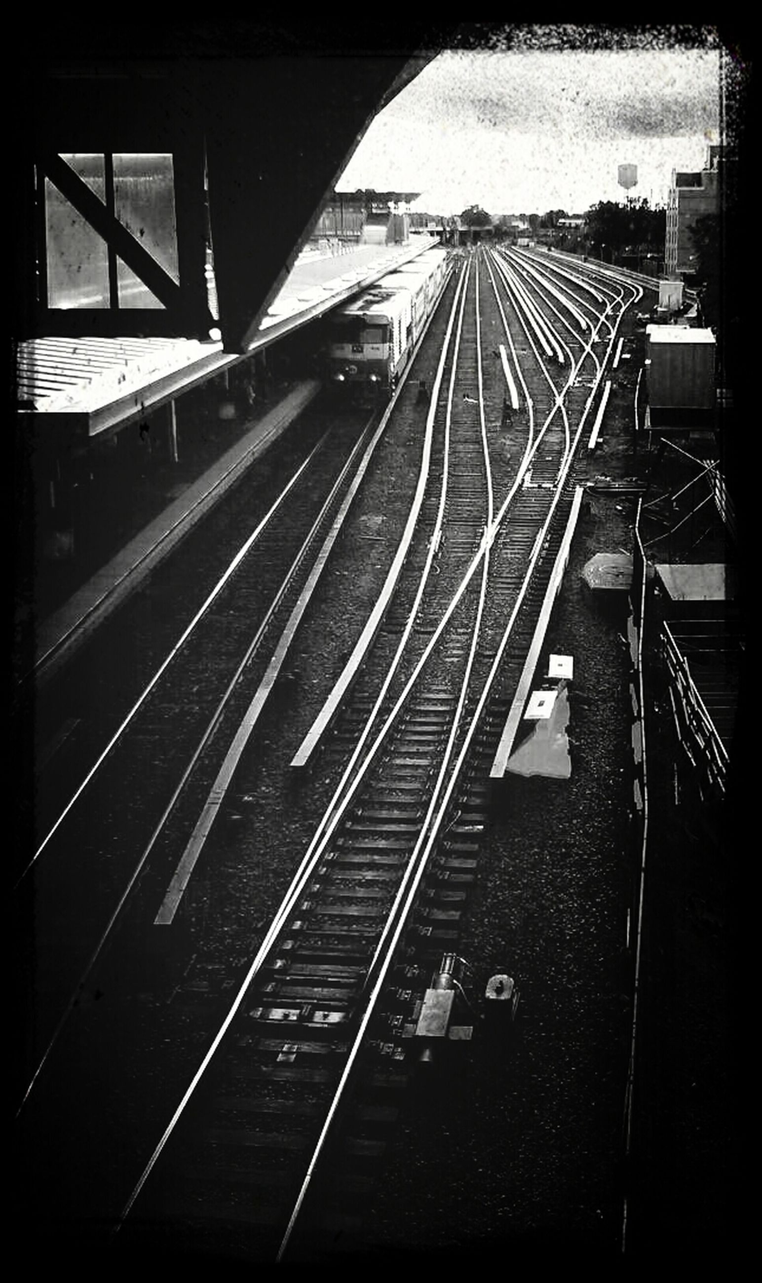 railroad track, transportation, rail transportation, railroad station platform, railroad station, public transportation, the way forward, transfer print, diminishing perspective, built structure, architecture, high angle view, auto post production filter, vanishing point, railway track, travel, sky, mode of transport, connection, train - vehicle
