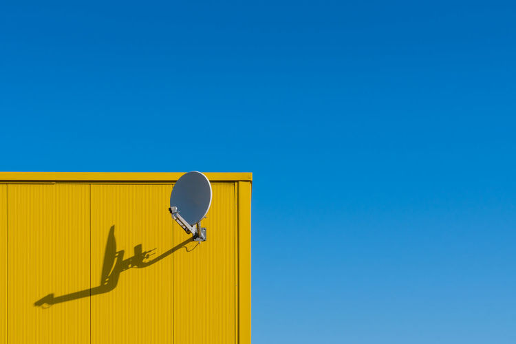 Low angle view of satellite dish at yellow wall against clear blue sky