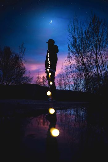 Silhouette man standing by illuminated tree against sky at night