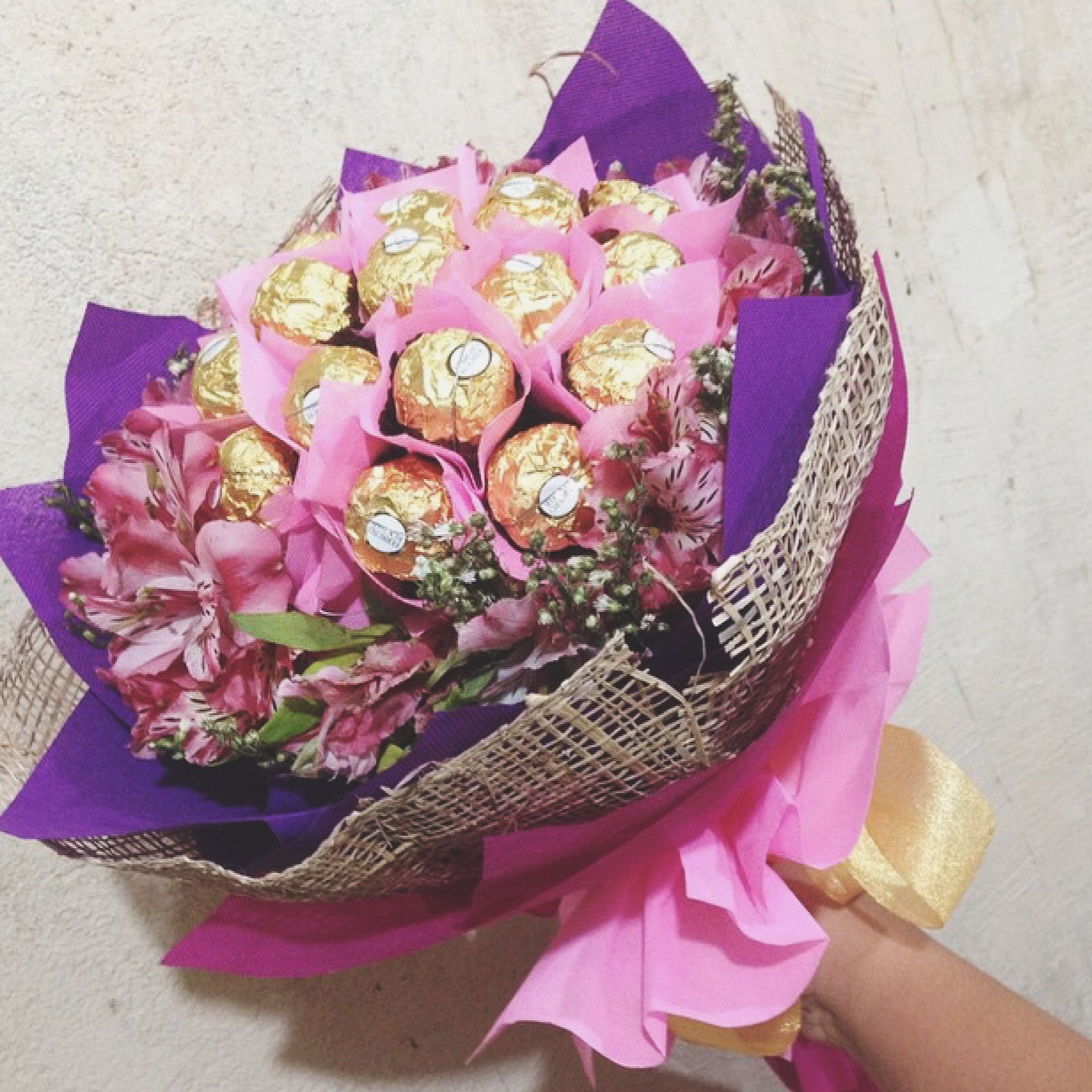 flower, indoors, pink color, bouquet, multi colored, petal, freshness, high angle view, fragility, decoration, wall - building feature, floral pattern, flower head, close-up, holding, fabric, art and craft, person