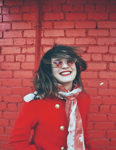 Smiling young woman wearing sunglasses against red brick wall