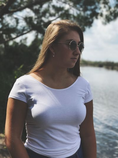 Young woman wearing sunglasses while standing by lake