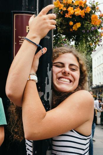 Cheerful young woman hugging lamp post