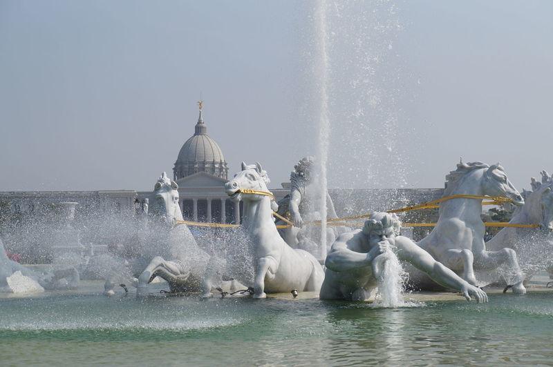 Water splashing in fountain against clear sky