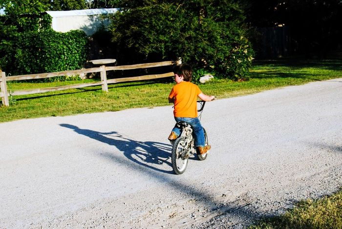The Color Of Sport Transportation Mode Of Transport Bicycle Land Vehicle Motion Road On The Move Riding Full Length Tree Boy Shadow Bycicle Children Childhood Travel Playing Cycling Casual Clothing Outdoors Green Color Park Journey Footpath