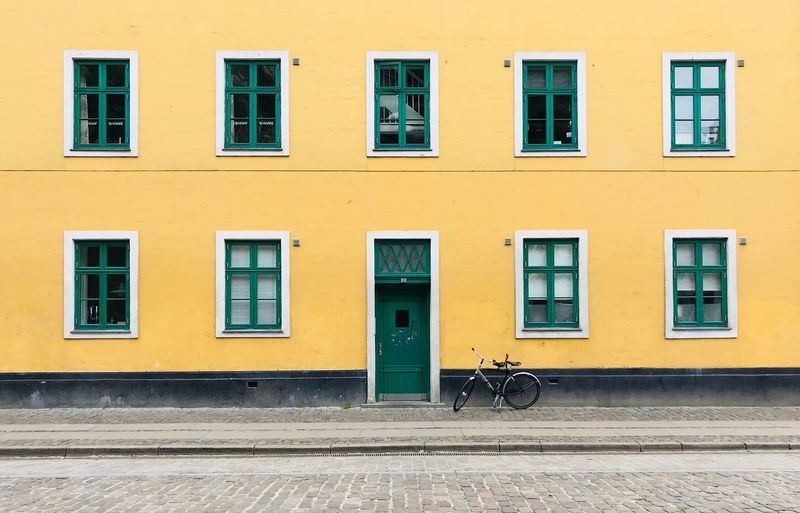 Bicycle Parked Against Yellow Building