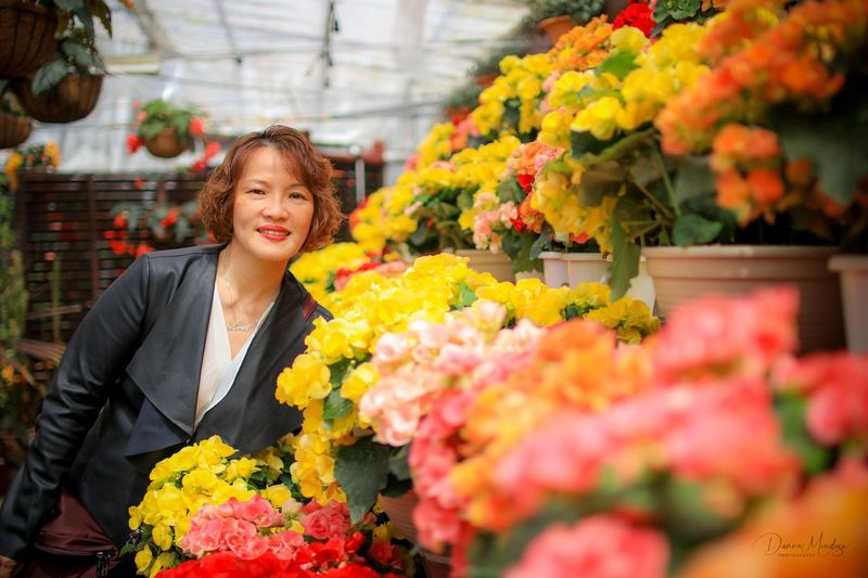 Portrait of smiling mature woman standing by colorful flowers in shop