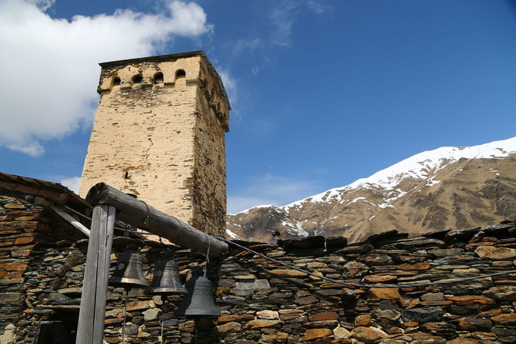 Sky Mountain Architecture Built Structure Day Nature Low Angle View Cloud - Sky History Cold Temperature No People Building Exterior Snow The Past Scenics - Nature Stone Wall Winter Building Wall Outdoors Snowcapped Mountain Georgia Mestia/town In Svaneti/Georgia