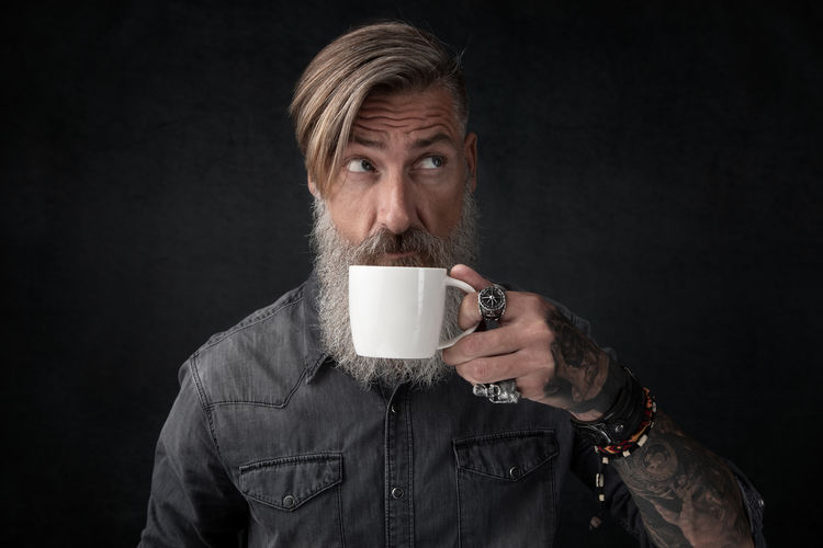 Thoughtful Hipster Man Drinking Coffee Against Black Background