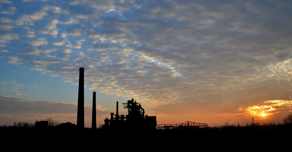 Silhouette smoke stack against sky during sunset