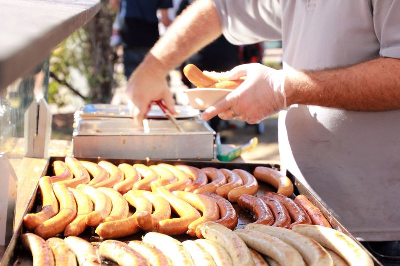 Midsection of man serving sausages at market stall