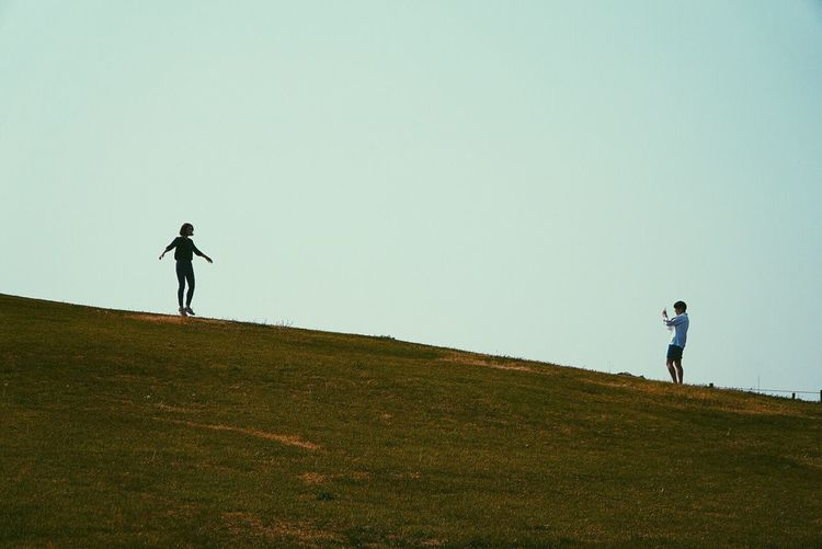 Man and woman standing on grassy hill against clear sky
