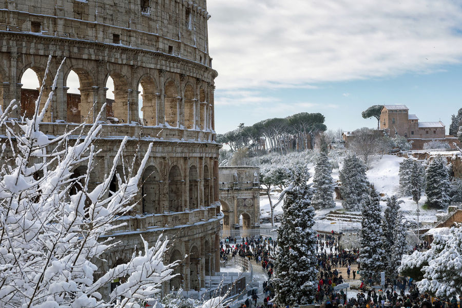Rome, Italy - February 26, 2018: An exceptional weather event causes a cold and cold air across Europe, including Italy. Snow comes in the capital, covering streets and monuments of a white white coat. In the picture, Colosseo comes alive with hundreds of people who went out to celebrate the event. Climatic Change Ice Winter Ancient Ancient Civilization Architecture Building Exterior Built Structure Cold Temperature Colosseum Day History Nature No People Old Ruin Outdoors Sky Snow Snow Covered Snowing Tourism Travel Destinations Tree Winter