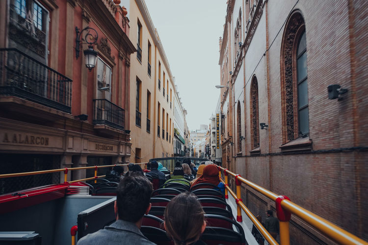 Rear view of people walking on canal amidst buildings in city