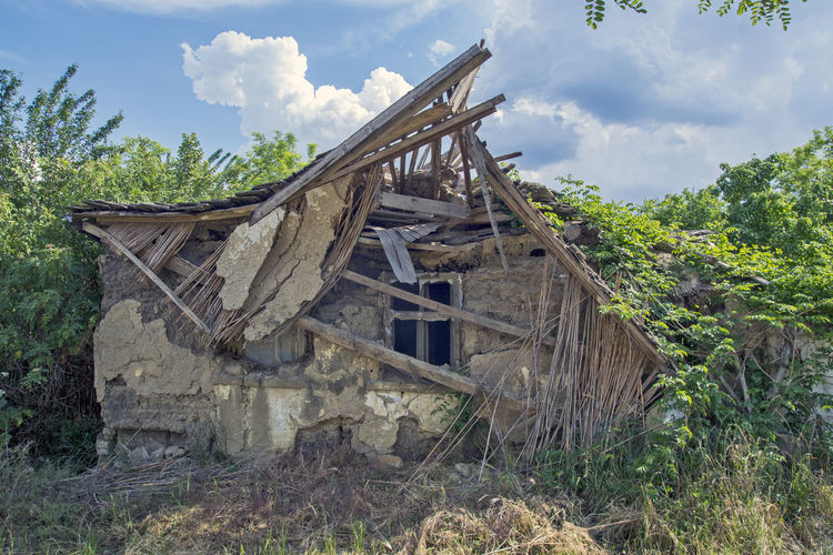 Abandoned wooden structure on field against sky