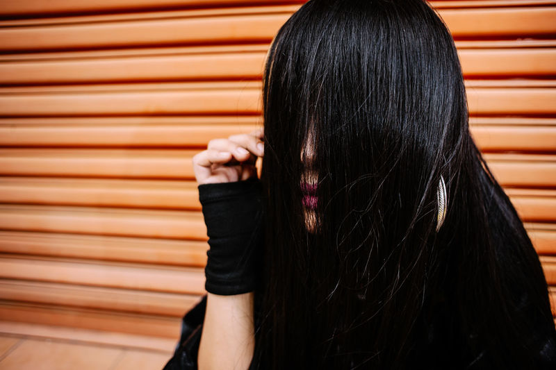 Close-Up Of Woman Covering Face With Hair Against Shutter Door