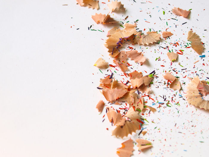 Colorful pencil shavings and pieces on white isolated background. Business Colored Isolated Wood Abstract Art And Craft Chip Close-up Creative Decoration Decorative Design Drawing Education Indoors  Material Messy Multi Colored Pencil Shavings School Sharpening Space For Text Still Life Studio Shot White Background