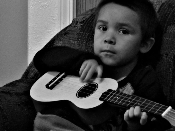 Close-up portrait of boy playing ukulele while sitting on sofa