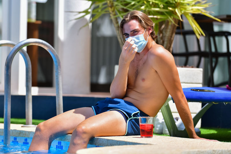 Shirtless man with protective face mask sitting in poolside of swimming pool