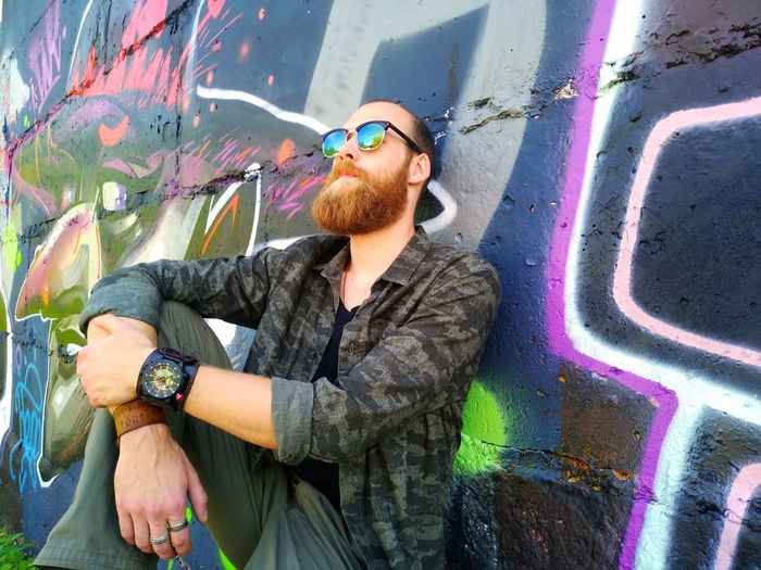 Young man wearing sunglasses standing against graffiti wall